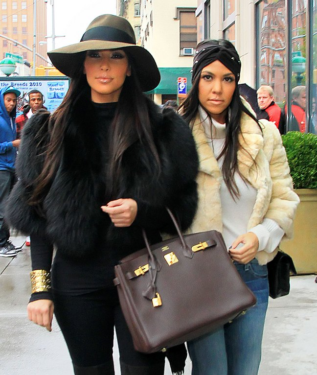 Kourtney Kardashian, cream faux fur jacket, head wrap, jeans, white turtleneck sweater, Kim Kardashian, black fur coat, gold bracelet, black pants, brown hat, brown bag