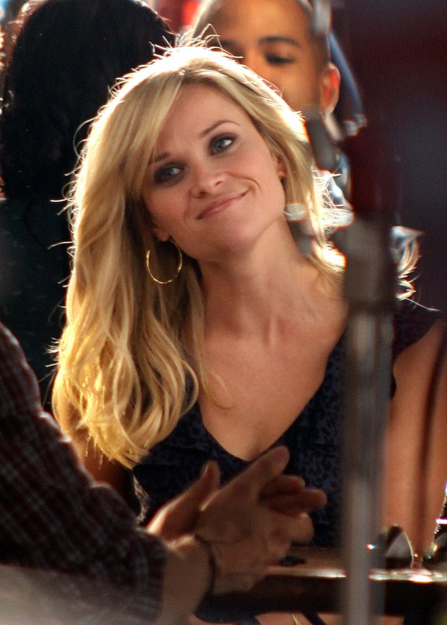 Reese Witherspoon, blue and black blouse, sleeveless blouse, gold hoop earrings, this means war