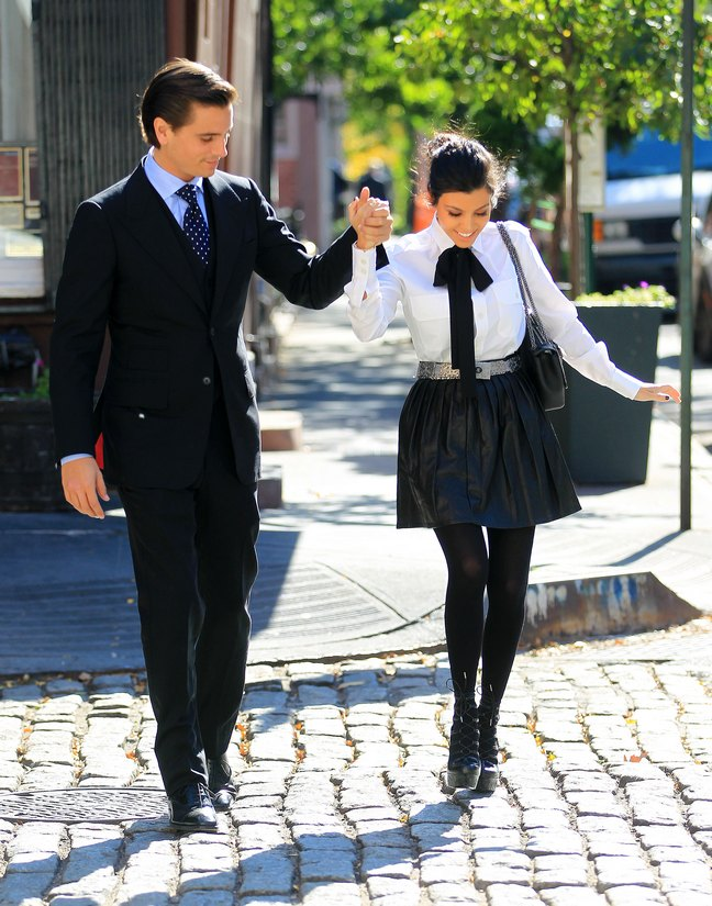Scott Disick, dark suit, Kourtney Karashian, white blouse, black tie bow, black mini skirt, black tights, black high heels