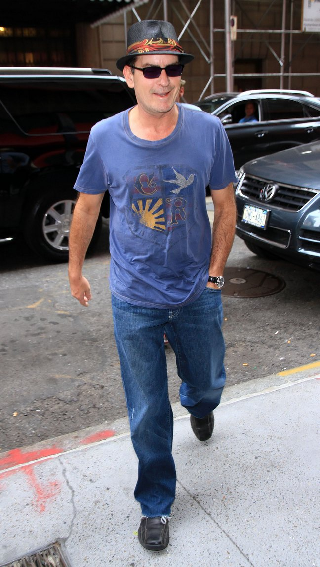 Charlie Sheen, black fedora, blue t-shirt, jeans, black shoes, sunglasses