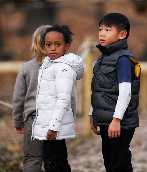 Zahara Jolie-Pitt, white winter coat, Pax Jolie-Pitt, black coat, white shirt