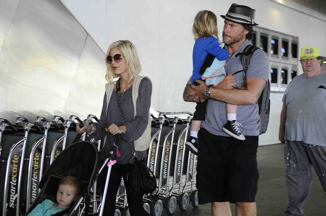 Tori Spelling gray blouse black jeans Dean Mcdermott hat